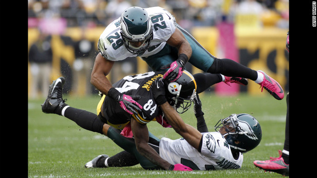 No. 29 Nate Allen and No. 24 Nnamdi Asomugha of the Eagles tackle Antonio Brown.