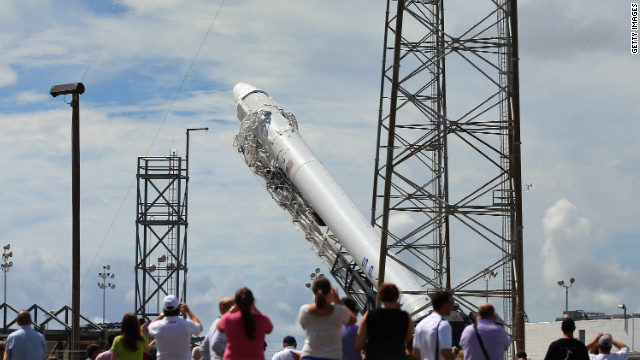 People watch as the SpaceX Falcon 9 rocket and its unmanned Dragon capsule are readied for launch Sunday in Cape Canaveral, Florida.