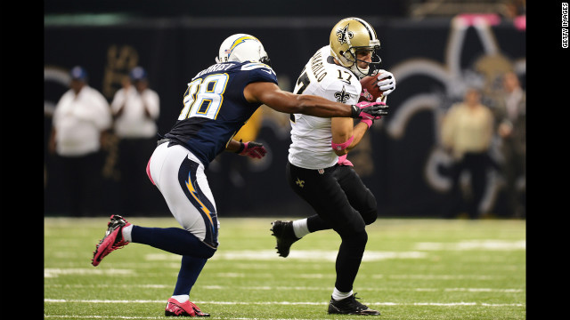 Saints wide receiver Greg Camarillo carries the ball as Marcus Gilchrist of the Chargers tries to make a tackle on Sunday.