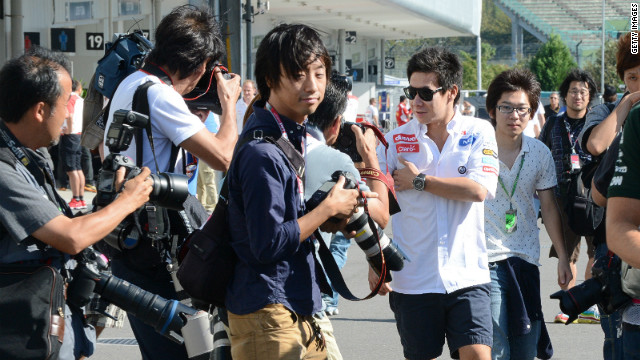 Sauber driver Kamui Kobayashi (white shirt) is the focus of constant media and public scrutiny as the 26-year-old walks in the paddock of the Suzuka circuit on Saturday ahead of the Japanese Grand Prix. 