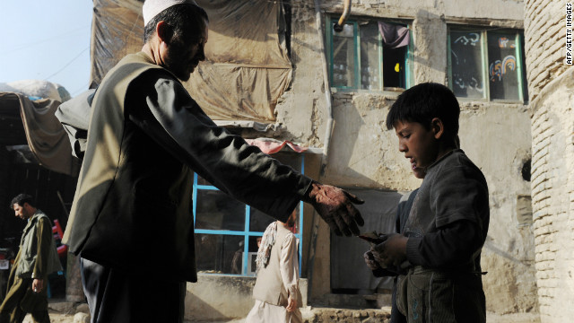An Afghan metal scrap merchant pays a rag-picker near a market in Kabul in September. Many in Afghanistan fear the economy, which depends on Western aid and companies, could collapse after NATO troops leave.