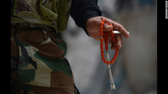 A Syrian rebel fighter holds a cigarette and prayer beads in Aleppo on Tuesday, October 9.