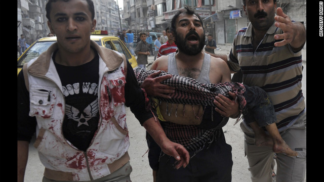 A Syrian man carries the body of his 5-year-old son, Mohammed Mustafa, outside a hospital after shelling by Syrian government forces in Aleppo on Tuesday.