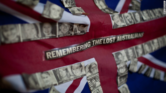 An Australian flag tied to a fence near the site of the blasts carries the photos of the 88 Australian victims of the attack. 