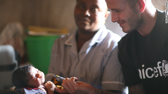 David Beckham touches the hand of two-day-old Mariatsu during a visit to the newborn's home in Sierra Leone.