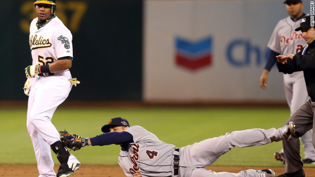 Yoenis Cespedes of the Oakland Athletics beats a tag by Omar Infante of the Detroit Tigers for a double in the first inning in Game Five of the American League Division Series Thursday at O.co Coliseum in Oakland, California.