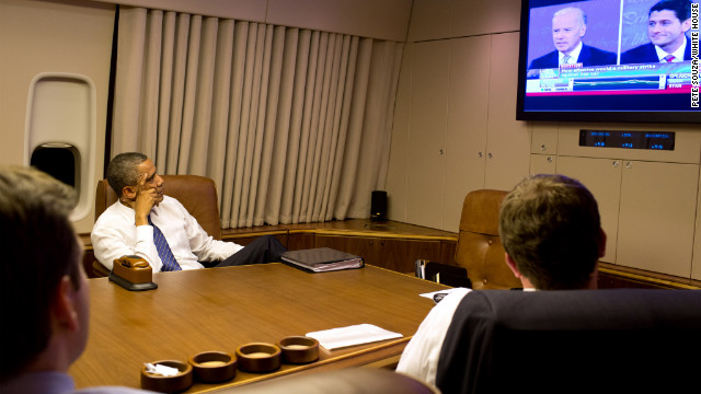 President Barack Obama watches the vice presidential debate aboard Air Force One with staff while heading home from Florida on Thursday.