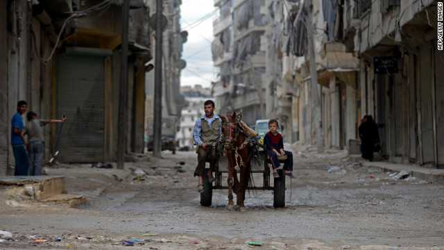 A Syrian man and boy ride a horse cart in Aleppo on Thursday.