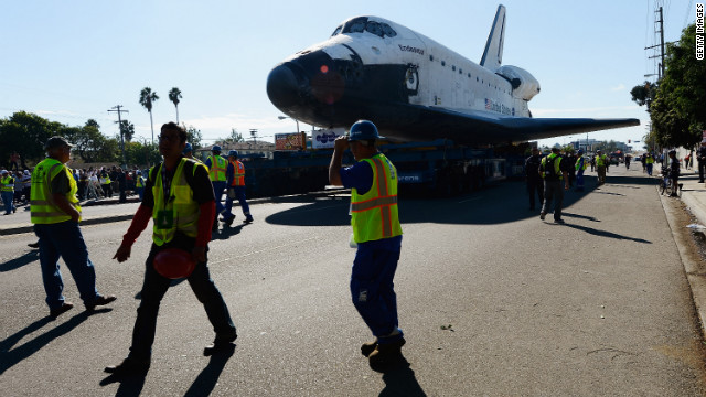 Workers escort Endeavour on its journey.