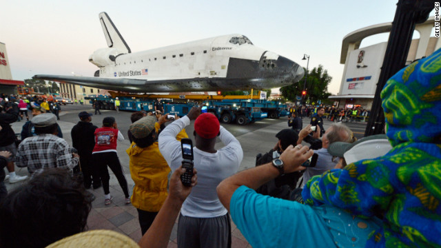Crowds look on as Endeavour is transported to The Forum arena before sunrise on Saturday.
