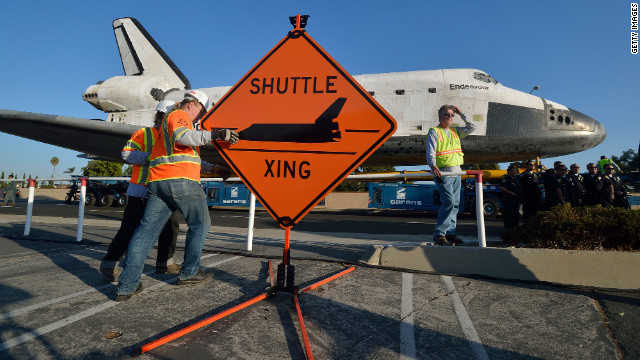 Work crews set up a &quot;Shuttle Xing&quot; sign on Saturday.