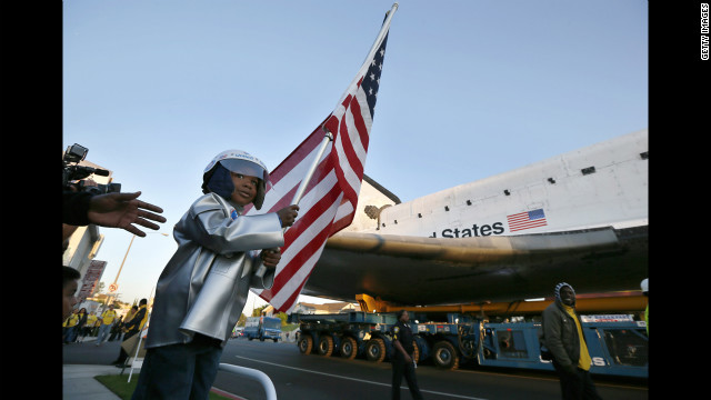Amir Morris, 3, holds an American flag as the shuttle passes by in Inglewood on Saturday.