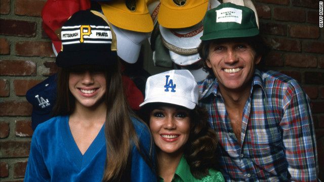 From left, Mary Clancy Collins and her parents, Mobley and Collins, pose for a portrait wearing baseball caps in their Los Angeles home, circa 1980.