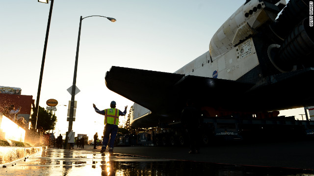 A worker accompanies the space shuttle Endeavour along Manchester Boulevard.