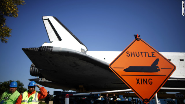 The space shuttle Endeavour passes a &quot;Shuttle crossing&quot; sign on its way to the California Science Center on Saturday in Inglewood, California. 