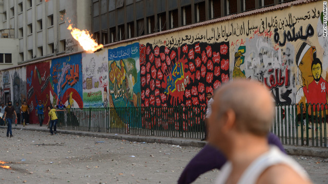 Egyptian opponents of the Muslim Brotherhood and President Mohamed Morsy throw a Molotov cocktail toward government supporters on Friday.
