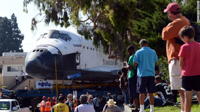 People watch as the shuttle makes its way up a narrow street.