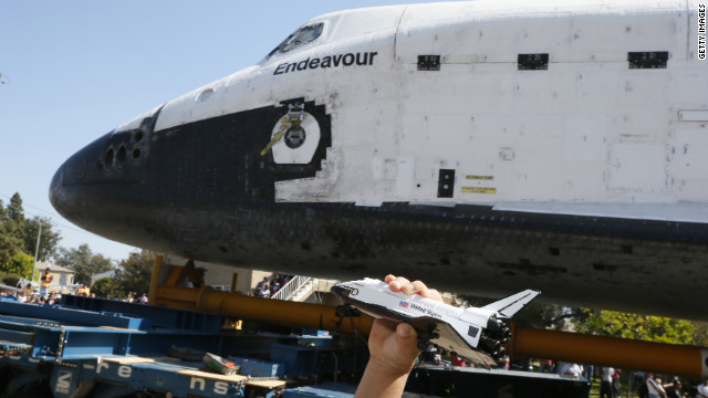 A boy holds a model of Endeavour as the real thing rolls past.