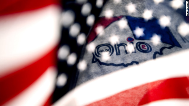 A supporter holds an American flag in front of the Ohio logo on his shirt as he stands with a crowd at Shawnee State University to hear Romney speak on Saturday.