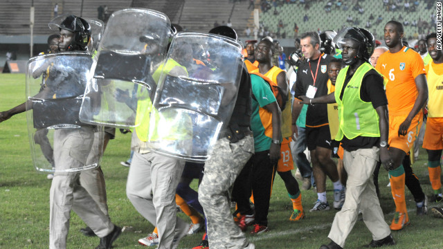 Ivory Coast's players are taken off the field under protection from riot police after the match against Senegal was abandoned.