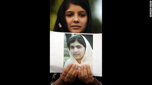 A Pakistani female activist holds a photograph of Malala and prays for her recovery in Islamabad on Saturday.