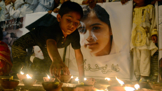 A Pakistani youth places an oil lamp next to a photograph of teen activist Malala Yousufzai on Friday, October 12, in Karachi, Pakistan.