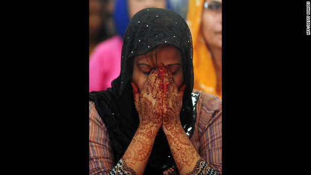 A Pakistani female covers her face during prayers in Karachi on Wednesday.