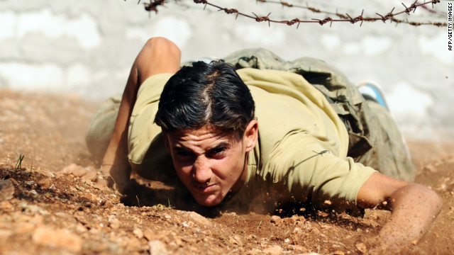 A Free Syrian Army fighter climbs under barbed wire as he trains at their camp in Syria's northwestern province of Idlib in an area under the control of rebel fighters on Monday.