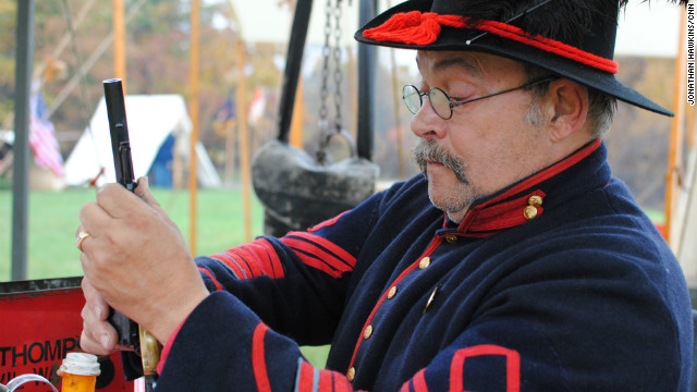 A U.S. civil war enthusiast cleans his pistol and prepares for a re-enactment battle in the swing-state of Iowa