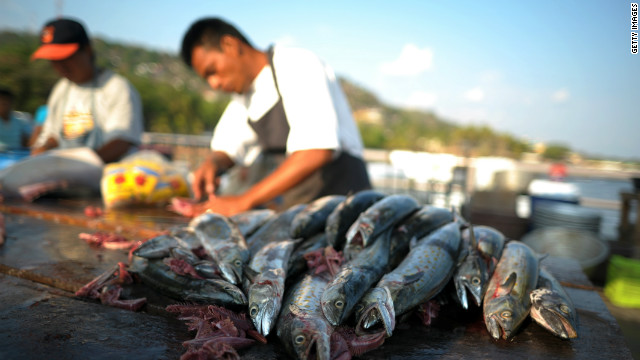 Fish mongers clean their catch in La Libertad, El Salvador. One of the benefits of traveling the world is experimenting with exotic, seasonal food, Kelly says. 