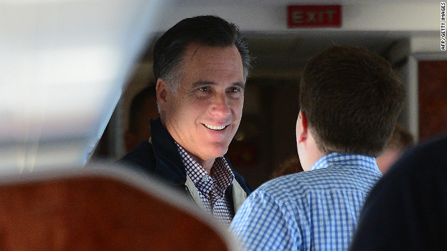 Republican presidential candidate Mitt Romney talks with aides aboard his campaign plane en route to Ronkonkoma, New York, on Tuesday.