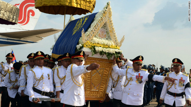 A Cambodian honor guard carries the coffin of the late former king towards a decorated hearse at the Phnom Penh International Airport on Wednesday.