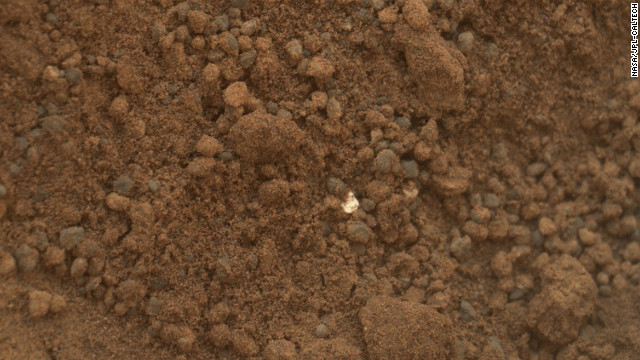 This image shows part of the small pit or bite created when NASA's Mars rover Curiosity collected its second scoop of Martian soil on October 15. The rover team determined that the bright particle near the center of the image was native to Mars, and not debris from the rover's landing.
