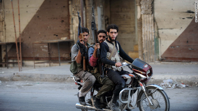 Syrian rebel fighters on Wednesday ride a motorcycle in Maaret al-Numan, an area under the control of rebel fighters in the northwestern Idlib province.