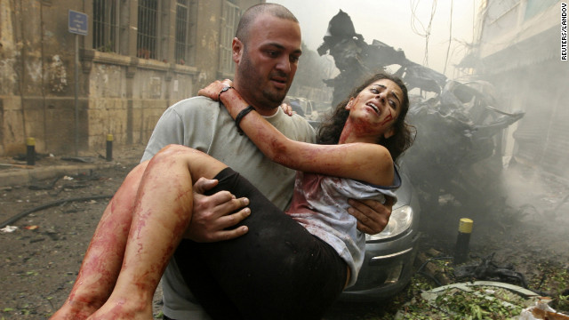 A wounded woman is carried from the area. The attack did not target any political figure, the Lebanese National News Agency says.
