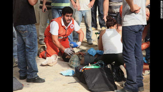 Lebanese Red Cross aid workers help a wounded man. Dozens were injured, some seriously, and others were slightly hurt, a senior hospital official said.
