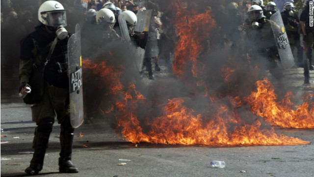 Protesters throw petrol bombs at riot police officers during strike on October 18, 2012 in Athens, Greece.