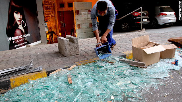 A worker on Saturday sweeps shattered glass outside damaged shops.