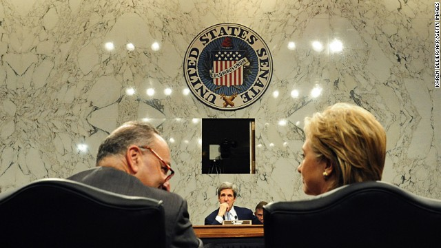 Sen. Charles Schumer, left, looks toward Secretary of State designate Clinton as Senate Foreign Relations Committee chairman Sen. John Kerry, center, looks on during nomination hearings January 13, 2009, on Capitol Hill.