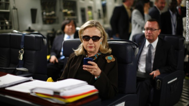 Clinton checks her PDA upon departure in a military C-17 plane from Malta bound for Tripoli, Libya, on October 18, 2011.
