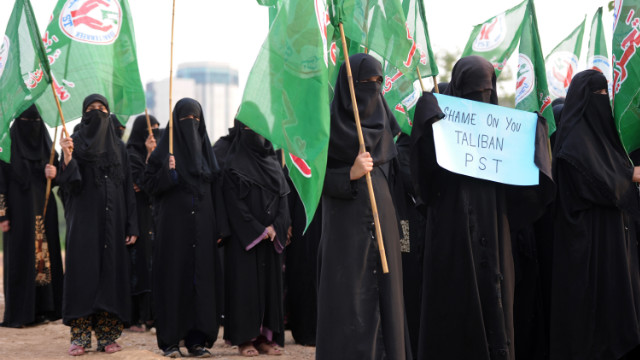 Pakistani activists of the Islamic Sunni Tehreek party carry flags at a rally in Islamabad on Sunday, October 14.