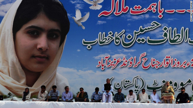 Pakistani leaders of the movement sit in front of a poster of Malala at a procession on Sunday in Karachi.