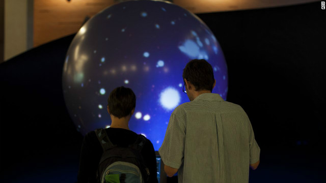 Two sci-fi enthusiasts interact with an exhibit called the &quot;Magic Planet&quot;at the Center for Science and the Imagination.