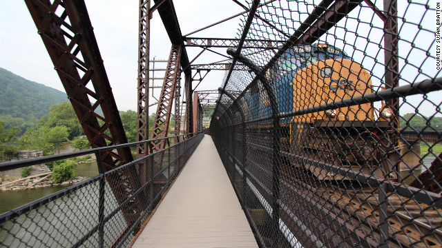 As hikers leave Harpers Ferry, West Virginia, and head for Maryland, they cross the Potomac River beside an active railroad bridge.