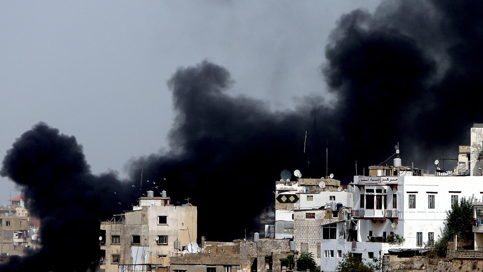 Smoke billows in Tripoli's Bab al-Tabanneh neighborhood during clashes between Alawites, an offshoot of Shiite Islam, and anti-government supporters on Monday, October 22. Fighting continued in Tripoli and Beirut, where a top police official was killed in a car bombing. At least two people were killed in Tripoli and several wounded in Beirut.