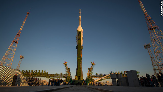 The Soyuz rocket is hoisted into position after being rolled out to the launch pad Sunday.