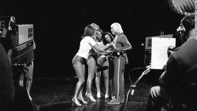 "Dancers on the BBC TV show ""Top of the Pops"" adjust Savile's track suit top for him during the making of the show in 1973."