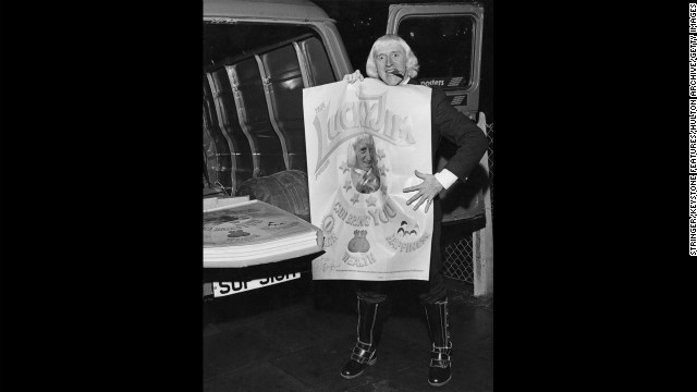 Savile holds a newly-printed &quot;Lucky Jim&quot; poster. The posters feature a portrait of the DJ, along with a text reading: &quot;The Lucky Jim poster can bring you health, wealth, happiness. This is a genuine duplicate signature and what's more Jimmy has actually touched YOUR poster!&quot;