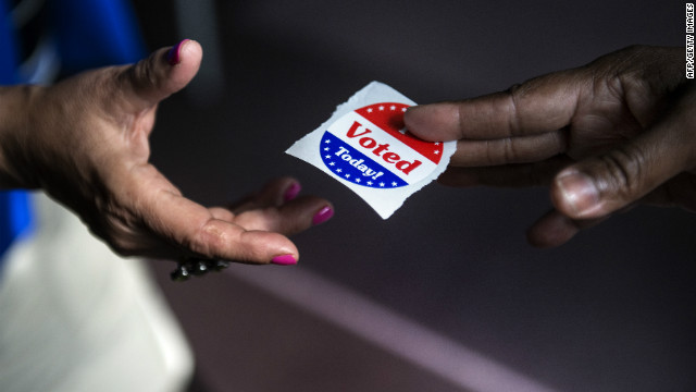 A poll worker hands out 'I Voted Today' stickers during the first day of early voting.