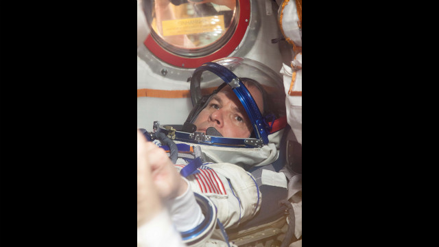 Ford straps into a seat of the Soyuz spacecraft on October 10 during the first of two &quot;fit check&quot; dress rehearsal sessions.